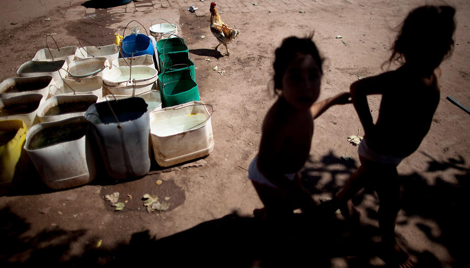 In this March 31, 2013, photo, Erika, left, and her twin sister Macarena, who suffer from chronic respiratory illness, play in their backyard near recycled agrochemical containers filled with water that is used for flushing their toilet, feeding their chickens and washing their clothes, near the town of Avia Terai, in Chaco province, Argentina. The twins' mother, Claudia Sariski, whose home has no running water, says she doesn't let her children drink the water from the discarded pesticide containers. (AP Photo/Natacha Pisarenko)