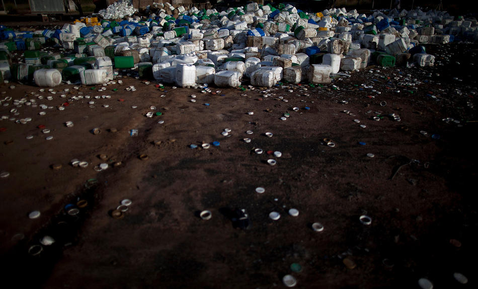 In this May 2, 2013 photo, empty agrochemical containers including Monsanto's Round Up products lay discarded at a recycling center in Quimili, Santiago del Estero province, Argentina. Instead of a lighter chemical burden in Argentina, agrochemical spraying has increased eightfold, from 9 million gallons in 1990 to 84 million gallons today. Glyphosate, the key ingredient in Monsanto's Round Up products, is used roughly eight to ten times more per acre than in the United States. Yet Argentina doesn't apply national standards for farm chemicals, leaving rule-making to the provinces and enforcement to the municipalities. The result is a hodgepodge of widely ignored regulations that leave people dangerously exposed. (AP Photo/Natacha Pisarenko)