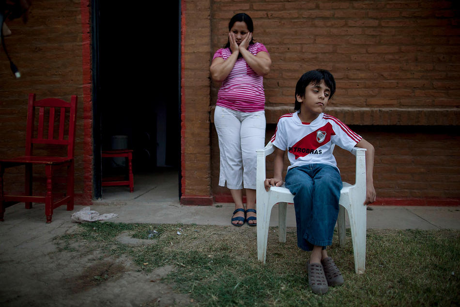 In this April 1, 2013, photo, Silvia Alvarez leans against her red brick home while keeping an eye on her son, Ezequiel Moreno, who was born with hydrocephalus, in Gancedo, in Chaco province, Argentina. Alvarez blames continuous exposure to agrochemical spraying for two miscarriages and her son's health problems. Chaco provincial birth reports show that congenital defects quadrupled in the decade after genetically modified crops and their related agrochemicals arrived. (AP Photo/Natacha Pisarenko)