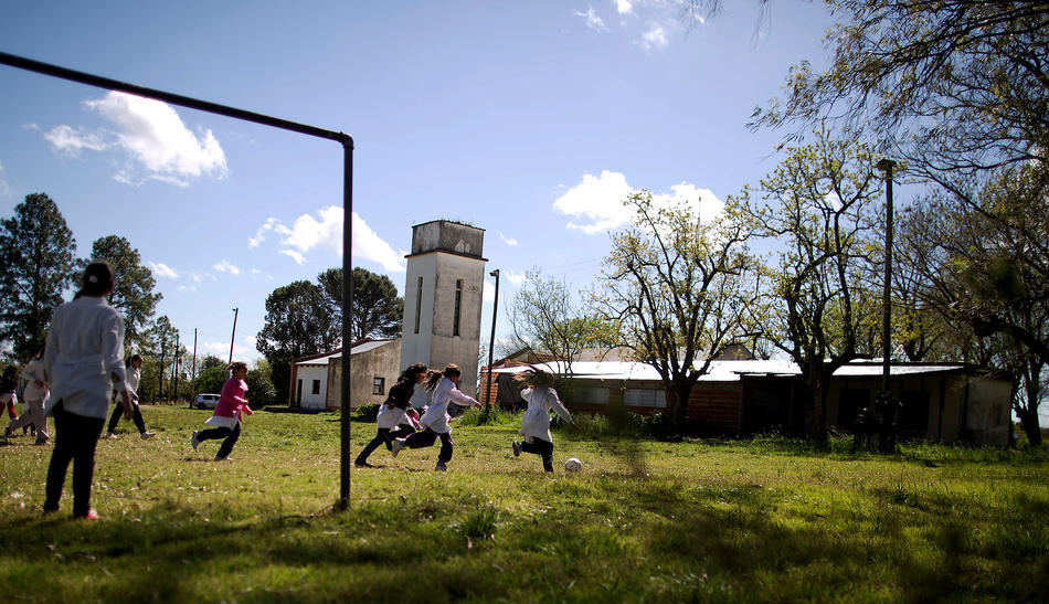In this Sept. 24, 2013 photo, students play soccer during recess at a rural school near Concepcion del Uruguay, Entre Rios province, Argentina. Teachers say the farm that abuts their school yard has been illegally sprayed with pesticides, even during class time. In Entre Rios, teachers reported that sprayers failed to respect legally required 50 meter setbacks outside 18 schools, and doused 11 of them while students were in session. Five teachers have since filed police complaints. (AP Photo/Natacha Pisarenko)