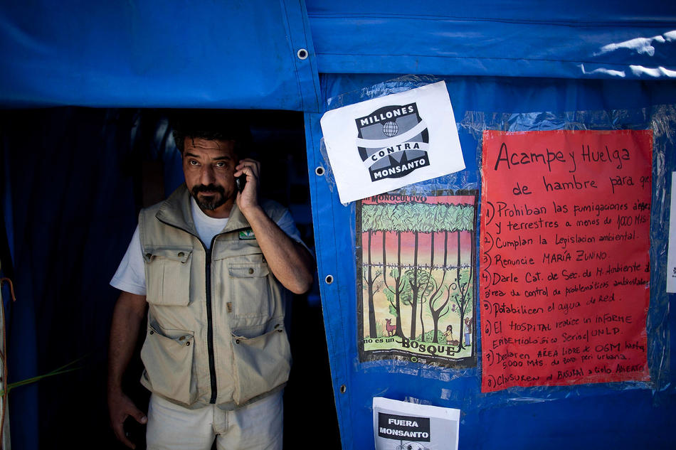 In this April 16, 2013, photo, activist Oscar Alfredo Di Vincensi talks on a cell phone inside his tent during his one-man hunger strike demanding that agrochemical spraying not be allowed within 1,000 meters of homes, in the main square of Alberti, in Buenos Aires province, Argentina. Earlier this year, Di Vincensi stood in a field waving a court order barring spraying within 1,000 meters of homes in his town of Alberti; a tractor driver doused him in pesticide. (AP Photo/Natacha Pisarenko)