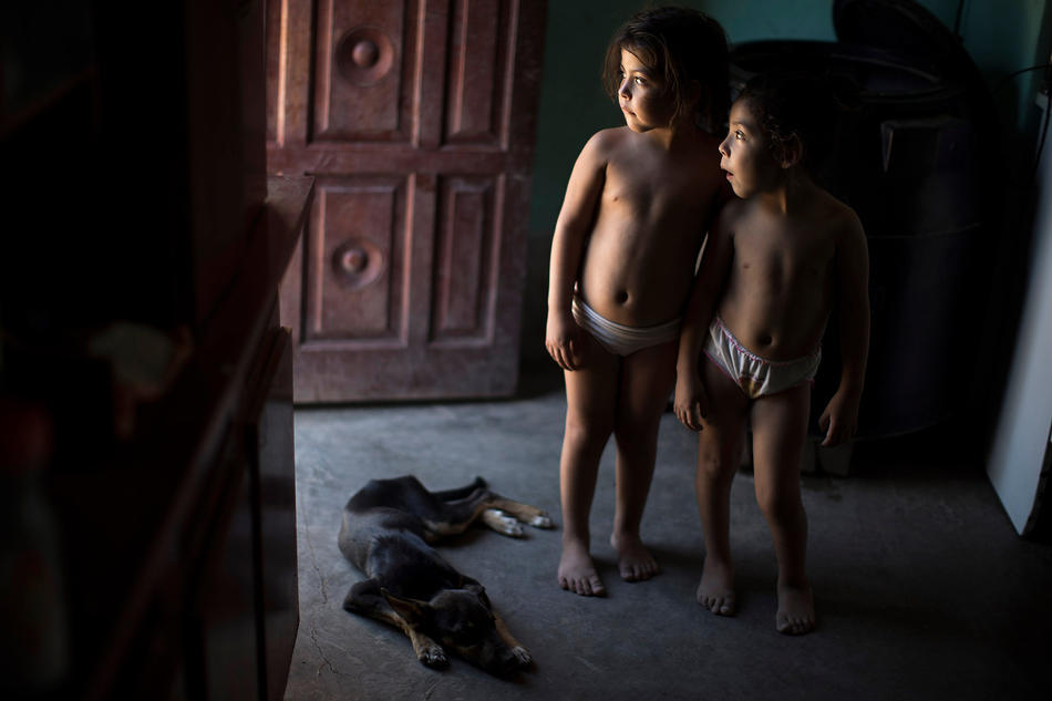 In this March 31, 2013, photo, Erika, right, and her twin sister Macarena, who suffer from chronic respiratory illness, stand inside their home in Avia Terai, in Chaco province, Argentina. The twins' mother, Claudia Sariski, whose home has no running water, says she doesn't let her children drink from the discarded pesticide containers she keeps in her dusty backyard. But her chickens do, and she has no other water to wash the family's clothes with. (AP Photo/Natacha Pisarenko)
