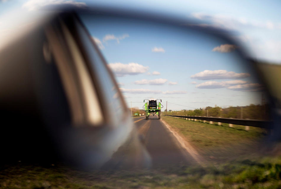 In this Sept. 24, 2013, photo, a tractor used for spraying agrochemicals is reflected in a car's side view mirror on a road in Parana, in Entre Rios province, Argentina. Glyphosate represents two-thirds of all agrochemicals used in Argentina, but resistance to pesticides is forcing farmers to mix in other poisons such as 2,4,D, which the U.S. military used in Vietnam War as an herbicide and defoliant.